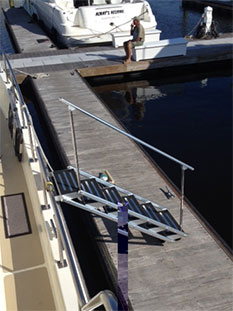 Aluminum folding yacht stairs with black non-skid steps.