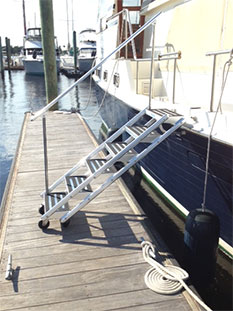 Non-skid yacht boarding steps attached to a yacht at a dock.
