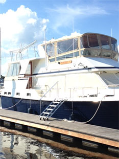 Yacht with boarding stairs attached at berth.