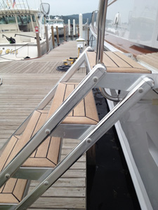 Yacht boarding stairs with teak steps attached to a yacht a dock.